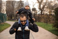 Father in eyeglasses carrying a little son on his shoulders. In the autumn park on the cloudy day Royalty Free Stock Photo
