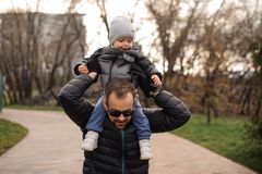Father in eyeglasses carrying little son on his shoulders. In the autumn park on the cloudy day Stock Photos