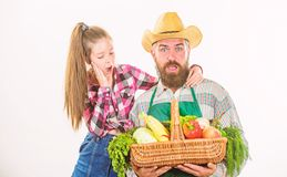 Father farmer or gardener with daughter hold basket harvest vegetables. Man bearded rustic farmer with kid. Family farm royalty free stock image