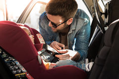 Father fasten his baby in car seat Stock Photography