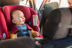 Father fasten his baby in car seat. Father fasten his little baby in the car seat stock images