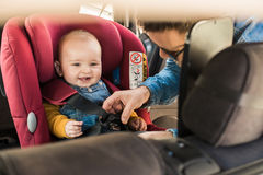 Father fasten his baby in car seat Stock Photo
