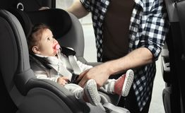 Father fastening baby to child safety. Seat inside car royalty free stock photo