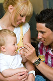 Father feeding a baby. Family portrait of father feeding his baby son held by the mother Royalty Free Stock Images