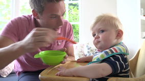 Father Feeding Baby Boy In High Chair Stock Images