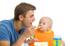 Father feeding baby boy Stock Photos