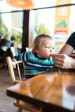 Father feeding baby boy with unhealthy food Stock Photos