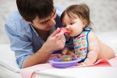 Father feeding baby girl at home Stock Photos