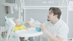 Father feeding baby sitting on high chair at home. Caring young dad clumsily feeding cute infant daughter with puree in nursery. Toddler girl with stained face stock footage