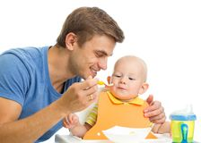 Father feeding baby son by healthy food Stock Image