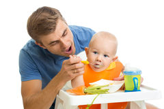 Father feeding baby son Stock Photo
