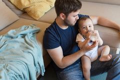 Father feeding baby. Young father feeding his baby with nursing bottle Stock Image