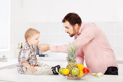 Father feeding child in kitchen. Father feeding child with apple in kitchen Stock Images