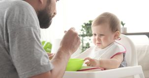 Father feeding crying baby daughter stock footage