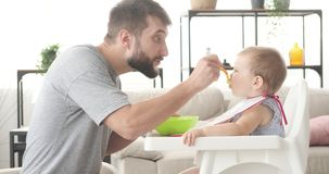 Father feeding cute baby daughter. Sitting on high chair stock footage