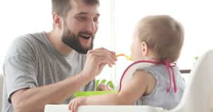 Father feeding cute baby daughter. Happy father feeding his cute baby daughter stock footage