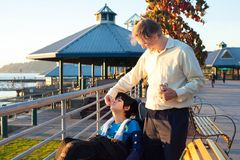 Father feeding disabled son in wheelchair at park royalty free stock photography