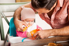 Father feeding his baby girl at home Stock Images