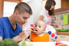 Father feeding his baby and mother cooking at. Father feeding his baby girl and mother cooking at kitchen Royalty Free Stock Images