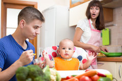Father feeding his baby while mother cooking at kitchen Stock Images