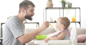 Father feeding his cute baby daughter. Sitting on high chair stock video