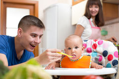 Father feeding his kid and mother cooking at kitchen. Dad feeding his kid and mother cooking at kitchen Stock Photography