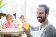 Father feeding his little baby daughter Stock Photos
