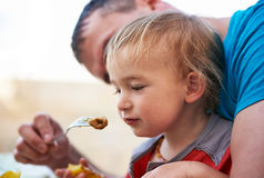 Father feeding his son Royalty Free Stock Images