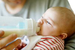 Father feeding newborn baby daughter with milk in nursing bottle Stock Image