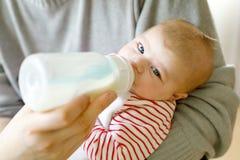 Father feeding newborn baby daughter with milk in nursing bottle Stock Photo