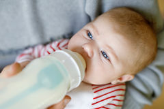 Father feeding newborn baby daughter with milk in nursing bottle. Formula drink for babies. New born child, little girl laying in bed. Family, new life royalty free stock image