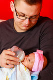 Father feeding newborn baby girl with milk bottle Stock Image