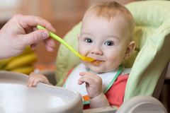 Father feeding small baby with spoon stock photos