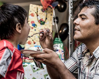 Father Feeding Son Birthday Cake. Latino father feeding his son a bite of birthday cake Stock Images