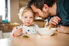 Father feeding a toddler boy at home. Paternity leave royalty free stock images