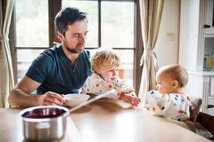 Father feeding two toddlers at home. Paternity leave Stock Image