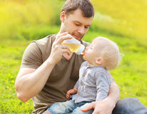 Father feeds baby from bottle on grass in summer Royalty Free Stock Images