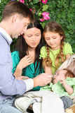 Father feeds baby and mother and little daughter look at baby Stock Photos