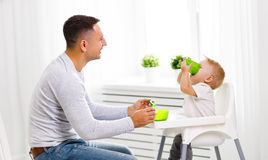 Father feeds baby from spoon Stock Photography