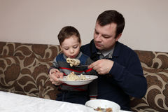 Father feeds his son. In the cafe Stock Photo
