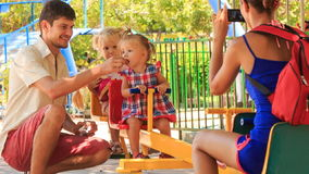Father feeds little girls on double swing mother takes pictures stock video footage