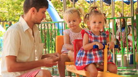 Father feeds little girls on double swing in tropical park stock video