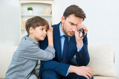 Father is feeling worry while son trying to comfort him Stock Image