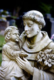 Father Figure. A Male guardian statue holding and protecting a young child in his arms Stock Photos
