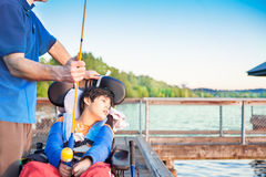 Father fishing off pier with disabled son in wheelchair Stock Photo