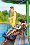Father fishing off pier with disabled son in wheelchair Stock Photography