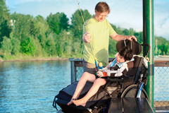 Father fishing off pier with disabled son in wheelchair Stock Photos