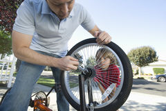 Father Fixing Son's Bicycle Tyre Stock Photography