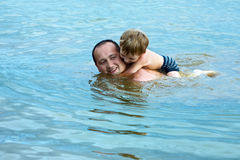 Father floats with the son Stock Photos