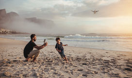 Father flying drone and son running on beach. Shot of young father flying drone and son running on beach. Young men flying drone and little boy running on the Stock Photos